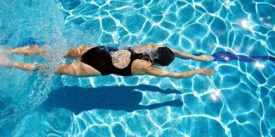 Hoy nos vamos a mojar y bien, porque con este artículo, empezamos una serie sobre la natación, sobre cuales son los beneficios de nadar, los distintos estilos, como un deporte tan completo puede ayudarnos en la rehabilitación de lesiones o sustituir a otros de mayor impacto, etc… He de reconocer que estoy muy ilusionado al hablar de la natación, un deporte muy completo, que podemos practicar todo el año, mas si vives en zonas de costa como yo, donde podemos disfrutar nadando en el mar desde abril hasta octubre y experimentar unas sensaciones únicas. Hay muchas razones para nadar Quizás podríamos hacer una lista infinita, de razones para ponerte el bañador y saltar a la piscina (o el mar), pero vamos a tratar de ver las más interesantes, las que mas beneficios a nivel muscular te pueden aportar, así que aquí tienes una lista que debería motivarte: Deporte de bajo impacto No hay impacto en el suelo cuando nadas, por lo que protegerás las articulaciones del estrés y la tensión muscular. De hecho, la Arthritis Foundation recomienda encarecidamente nadar y realizar actividades acuáticas. Las clases de aeróbicos acuáticos tipo aqua fitness, son también súper interesante, porque incluso si saltas o impactas con el fondo de la piscina, lo haces con menos fuerza porque está flotando en el agua. No sólo eso, sino que si usas un dispositivo de flotación tipo pull, el impacto es aún menor. Se puede nadar a cualquier edad Debido a que no hay impacto con la natación, puedes continuar durante toda la vida, da igual la edad que tengas, desde recién nacido, hasta personas de la tercera edad, puedes disfrutar de la natación. Navegando por internet he encontrado un grupo de edades de 100 a 104 años! Y el maestro de la Formacion física, Jack La Lanne, que murió en 2011, según se dice, aún nadaba una hora cada día a la edad de 93 años! Nadando mejoras tu resistencia cardiovascular La natación mejora la resistencia. En un estudio de hombres y mujeres sedentarios de mediana edad que hicie